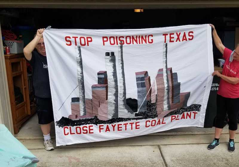 "Two people holding up a banner stating ""Stop Poisoning Texas, Close Fayette Coal Plant"""""